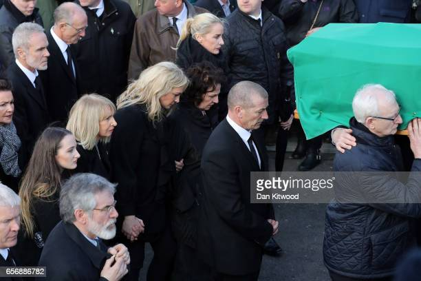 Daughters Fionnuala McGuinness Grainne McGuinness and wife Bernadette McGuinness walk behind the coffin of the late Martin McGuinness to the Derry...