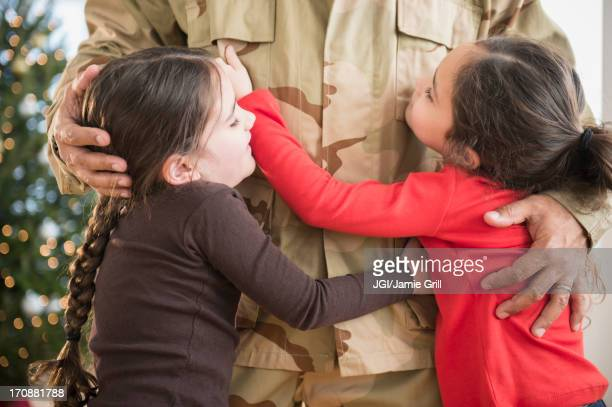 Daughters hugging soldier father