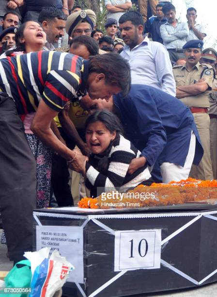 Daughters of martyr Sanjay Kumar who was killed in Maoist attack in Sukma Chhattisgarh wail near his body during his funeral at his native village...
