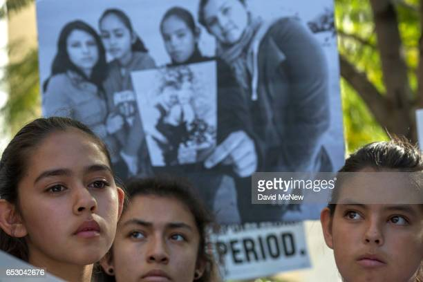 Daughters of Romulo AvelicaGonzalez Fatima Yunleni and Diana stand near a family photo as loved ones and supporters rally for his release outside US...