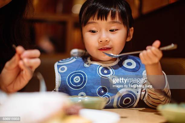 Daughtger having meal in restaurant with mom