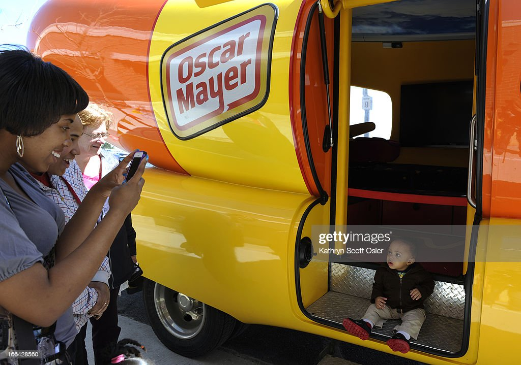 Daushawnae Coleman, left, standing with her mother, Ernestine Barrett, second from left, takes a photo of her baby brother Brandon Barrett, Jr.,1, inside the Wienermobile. The Oscar Mayer Wienermobile rolls through the metro area on its voyage across the country celebrating the 25th anniversary of having the giant hot dog piloted by recent college grads. The grads, who are part of the 'hotdogger tradition', must attend two weeks of 'Hotdog High' in Madison Wisconsin and serve as drivers and ambassadors of all things Oscar Mayer for one year. There is still a chance to see the road dog before it hits the highway on its return to Wisconsin from 11 a.m.- 4 p.m Saturday at the Walmart at 440 Wadsworth Blvd. in Lakewood.