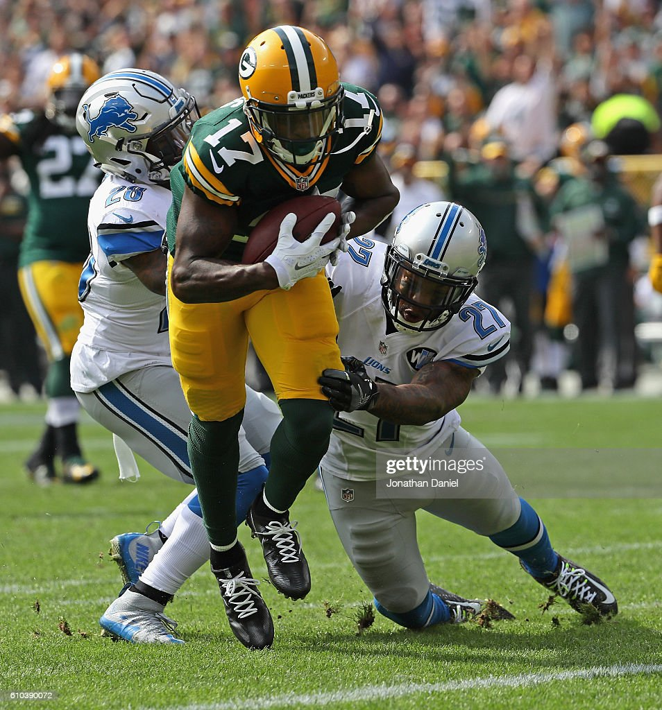 Davante Adams #17 of the Green Bay Packers breaks a tackle attempt by Glover Quin #27 and Quandre Diggs #28 of the Detroit Lions to score a first quarter touchdown at Lambeau Field on September 25, 2016 in Green Bay, Wisconsin.