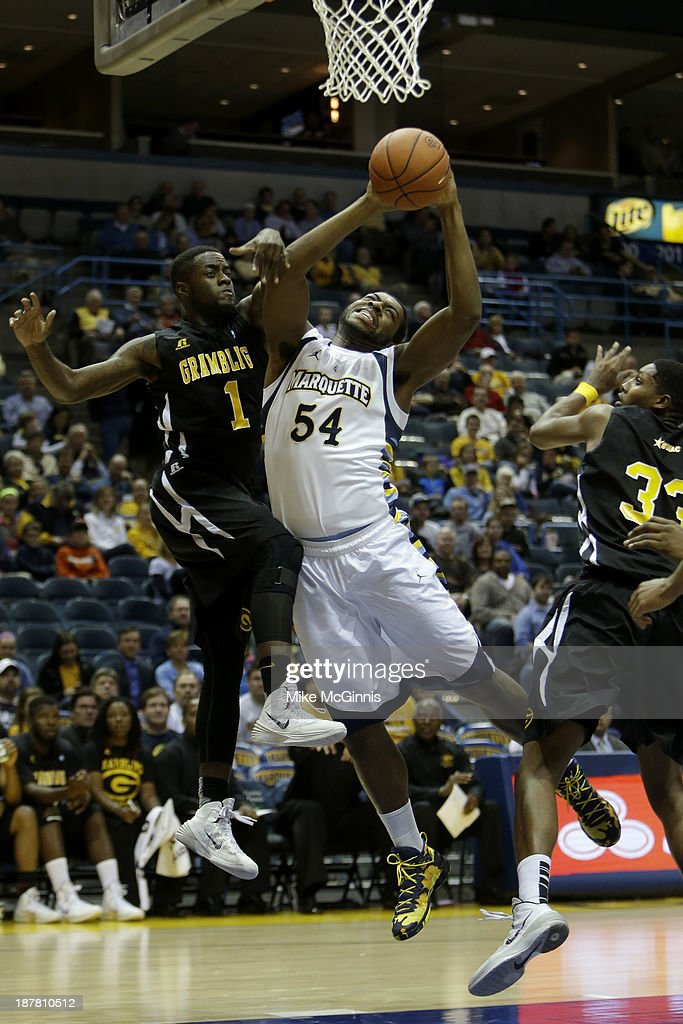 Davante Gardner #45 of the Marquette Golden Eagles draws the foul driving to the hoop on A'Torri Shine #1 of the Grambling State Tigers during the first half at BMO Harris Bradley Center on November 12, 2013 in Madison, Wisconsin.