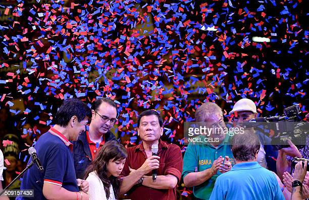 Davao City mayor and presidential candidate Rodrigo Duterte is greeted by his political allies during his party's proclamation rally in Manila on...