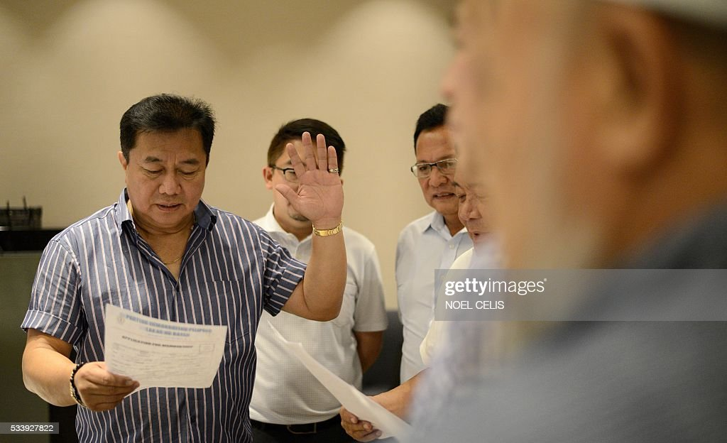 Davao Del Norte Representative Pantaleon Alvarez (L) of the Partido Demokratiko Pilipino-Lakas ng Bayan (PDP-Laban) officiates the oath taking of Mindanao lawmakers as new members of PDP-LABAN, the political party of Philippines' president-elect Rodrigo Duterte, at a hotel in Manila on May 24, 2016. Business titans, turncoat politicians, celebrities and rebel leaders are descending on the long-neglected far southern Philippines, hoping to gain favour with the nation's shock new powerbroker. The remote and dusty city of Davao has suddenly become the country's new seat of power after hometown hero Rodrigo Duterte won last week's presidential election in a landslide. / AFP / NOEL