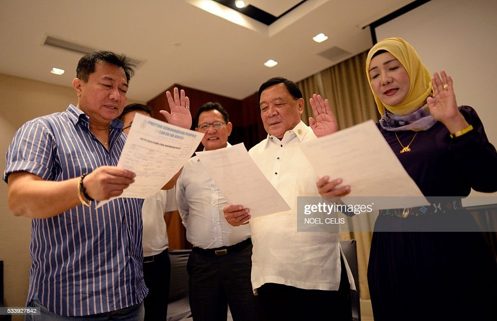Davao Del Norte Representative Pantaleon Alvarez (L) of the Partido Demokratiko Pilipino-Lakas ng Bayan (PDP-Laban) officiates the oath taking of Mindanao lawmakers as new members of PDP-LABAN, the political party of Philippines' president-elect Rodrigo Duterte in Manila on May 24, 2016. Business titans, turncoat politicians, celebrities and rebel leaders are descending on the long-neglected far southern Philippines, hoping to gain favour with the nation's shock new powerbroker. / AFP / NOEL