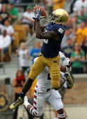 DaVaris Daniels of the Notre Dame Fighting Irish catches a touchdown pass over Anthony Robey of the Temple Owls at Notre Dame Stadium on August 31...