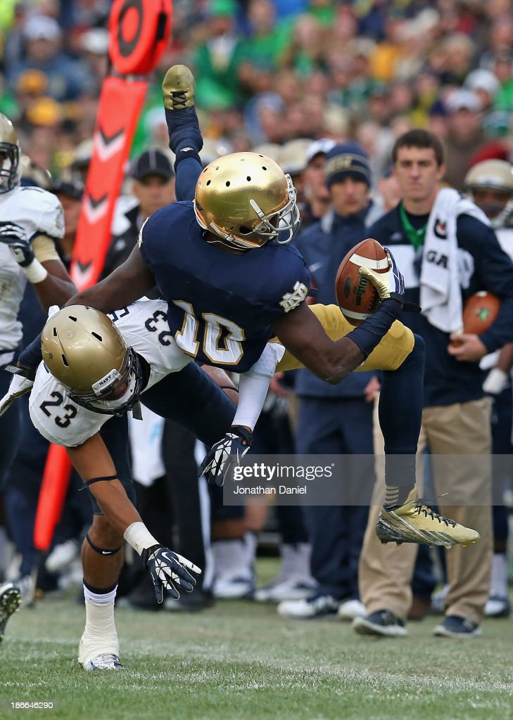 DaVaris Daniels of the Notre Dame Fighting Irish is upended by Chris Ferguson of the Navy Midshipmen at Notre Dame Stadium on November 2 2013 in...