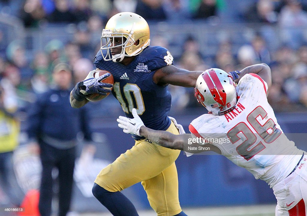 DaVaris Daniels #10 of the Notre Dame Fighting Irish runs the ball against Johnathan Aiken #26 of the Rutgers Scarlet Knights during the New Era Pinstripe Bowl at Yankee Stadium on December 28, 2013 in the Bronx Borough of New York City.
