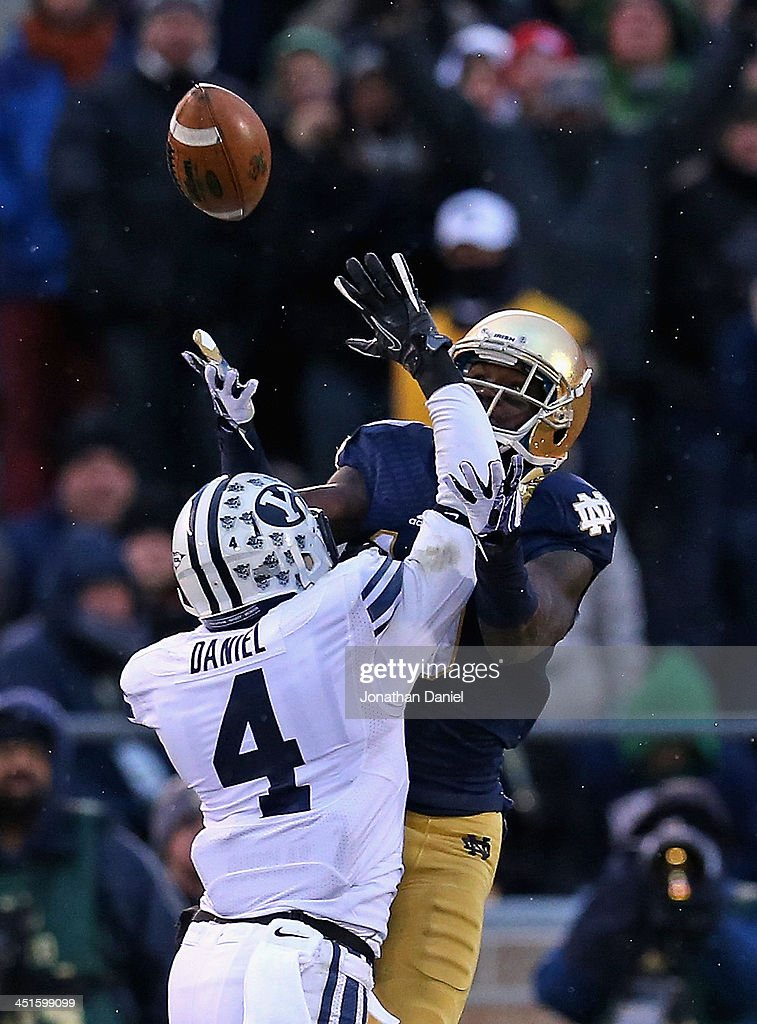 DaVaris Daniels of the Notre Dame Fighting Irish tirews toi make a catch under pressure from Robertson Daniel of the Brigham Young Cougars at Notre...