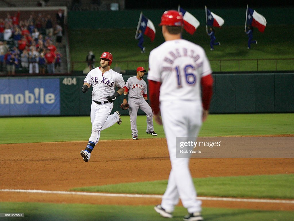 Dave Anderson #16 of the Texas Rangers looks on as <a gi-track='captionPersonalityLinkClicked' href=/galleries/search?phrase=Mike+Napoli&family=editorial&specificpeople=525007 ng-click='$event.stopPropagation()'>Mike Napoli</a> #25 runs the bases after hitting a three run home run in game two of the double header against the Los Angeles Angels of Anaheim at Rangers Ballpark in Arlington on September 30, 2012 in Arlington, Texas.