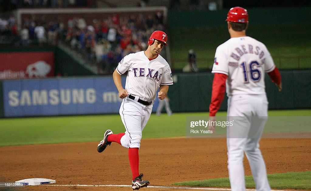 Dave Anderson #16 third base coach congratulates David Murphy #7 of the Texas Rangers for scoring on a three run home run hit by Mike Napoli #25 in game two of the double header against the Los Angeles Angels of Anaheim at Rangers Ballpark in Arlington on September 30, 2012 in Arlington, Texas.