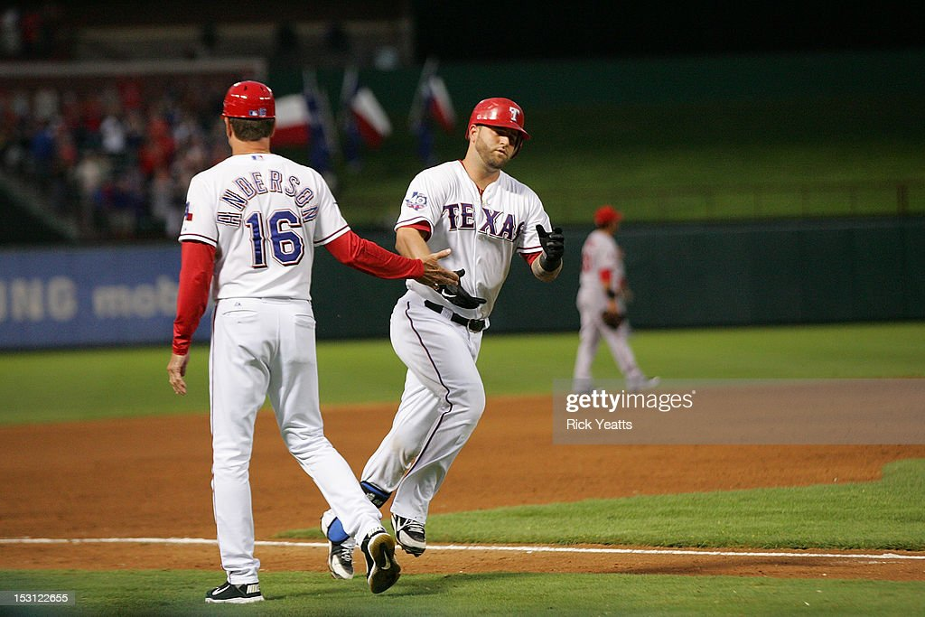 Dave Anderson #16 third base coach congratulates Mike Napoli #25 in game two of the double header for hitting a three run home run against the Los Angeles Angels of Anaheim against the Los Angeles Angels of Anaheim at Rangers Ballpark in Arlington on September 30, 2012 in Arlington, Texas.