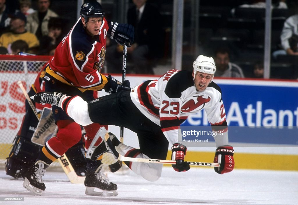 Dave Andreychuk #23 of the New Jersey Devils looks to be tripped up by Gord Murphy #5 of the Florida Panthers circa 1999 at the Continental Airlines Arena in East Rutherford, New Jersey.
