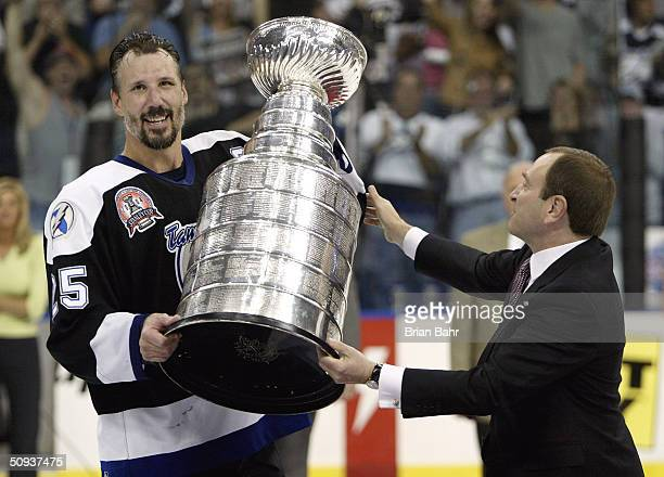 Dave Andreychuk of the Tampa Bay Lightning is presented with the Stanley Cup by NHL Commisioner Gary Bettman after defeating the Calgary Flames in...