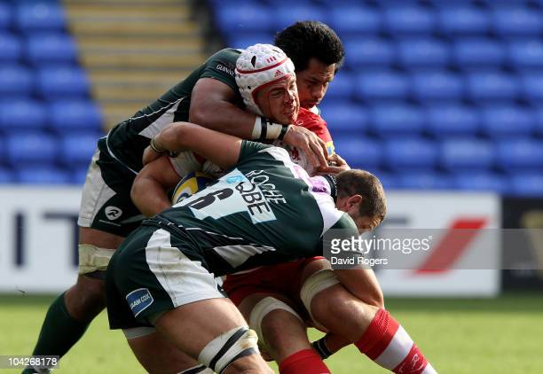 Dave Attwood of Gloucester is tackled by George Stowers and Kieran Roche during the Aviva Premiership match between London Irish and Gloucester at...