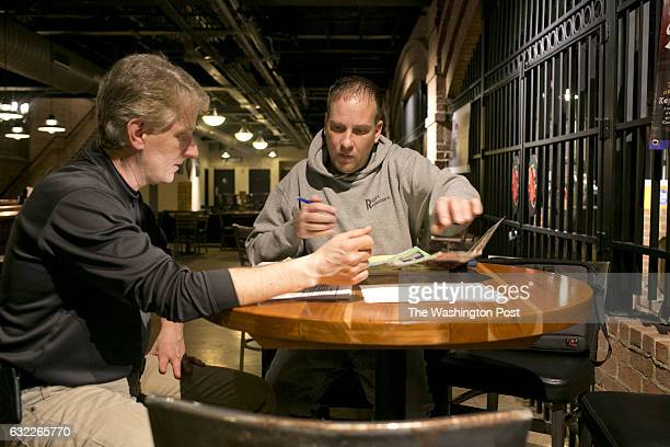 Dave Beule left and Ralph Case right go over logistics for the bus ride at Beule's brewery Snorky's in Canton Ohio on January 16 2017 Ralph Case has...