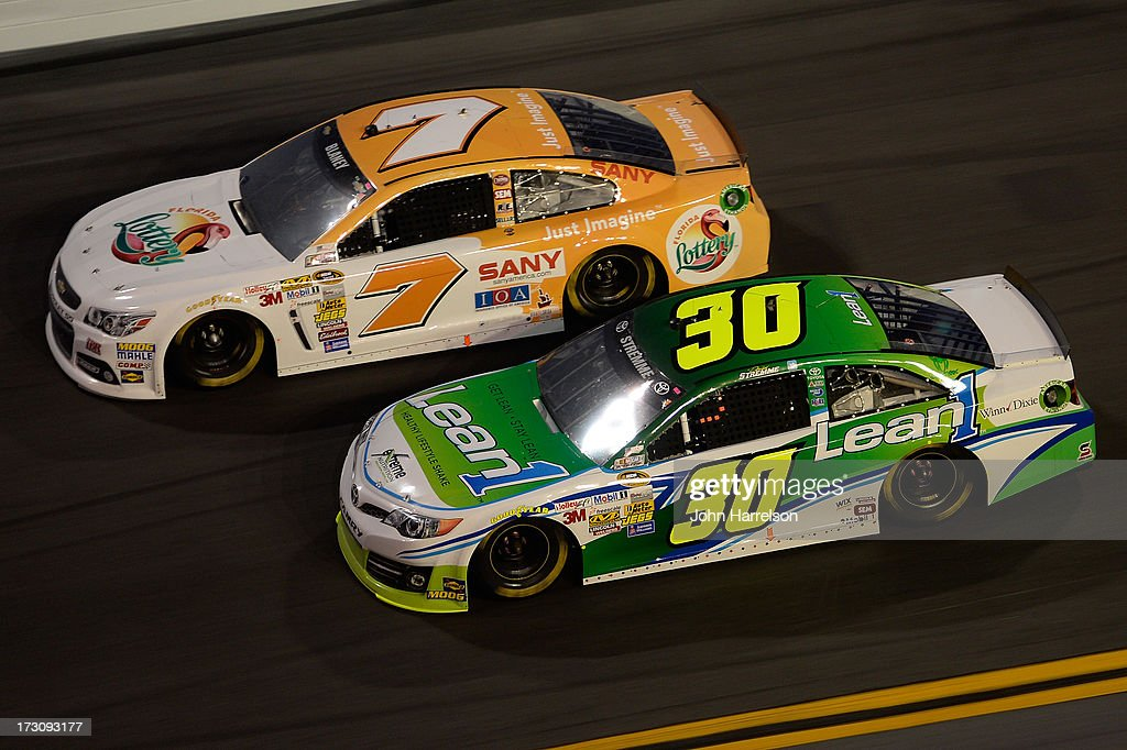 Dave Blaney, driver of the #7 Florida Lottery Chevrolet, races David Stremme, driver of the #30 Lean 1 Toyota, during the NASCAR Sprint Cup Series Coke Zero 400 at Daytona International Speedway on July 6, 2013 in Daytona Beach, Florida.