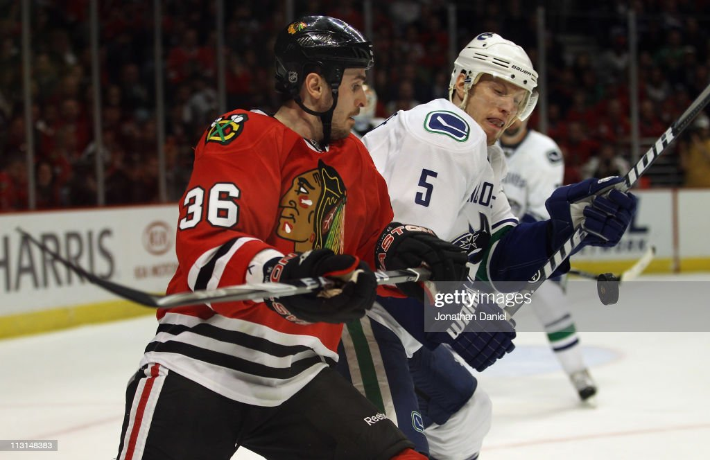 Dave Bolland and Christian Ehrhoff of the Chicago Blackhawks of the Vancouver Canucks battle for the puck in Game Six of the Western Conference...