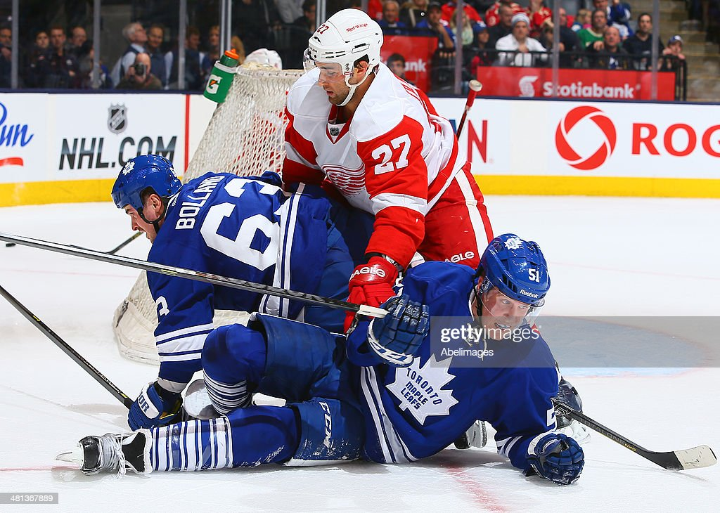 Dave Bolland #63 and Jake Gardiner #51 of the Toronto Maple Leafs get held up by Kyle Quincey #27 of the Detroit Red Wings during NHL action at the Air Canada Centre March 29, 2014 in Toronto, Ontario, Canada.