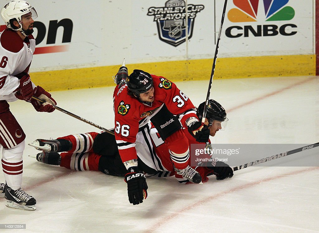 Dave Bolland of the Chicago Blackhawks falls over Duncan Keith next to David Schlemko of the Phoenix Coyotes in Game Six of the Western Conference...