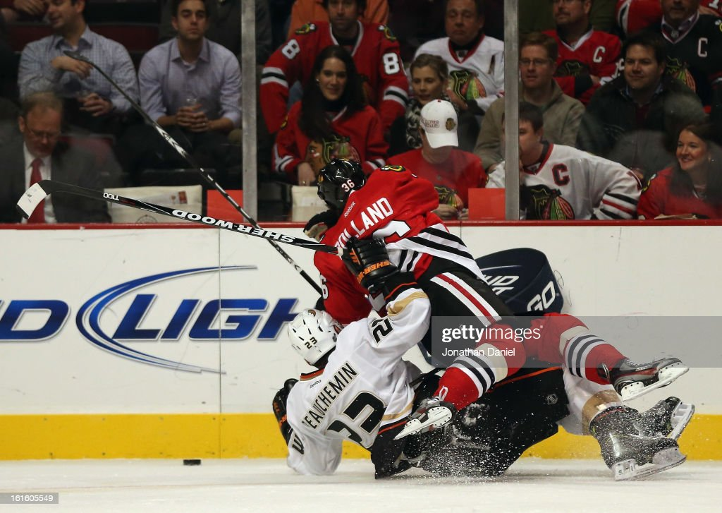 Dave Bolland of the Chicago Blackhawks gets dumped by Francois Beauchemin of the Anaheim Ducks as they battle for the puck at the United Center on...