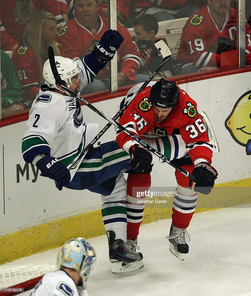 Dave Bolland of the Chicago Blackhawks hits Dan Hamhuis of the Vancouver Canucks in Game Six of the Western Conference Quarterfinals during the 2011...
