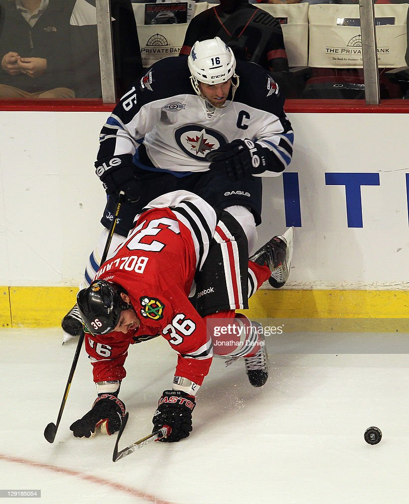 Dave Bolland of the Chicago Blackhawks hits the ice trying to keep the puck away from Andrew Ladd of the Winnipeg Jets at the United Center on...