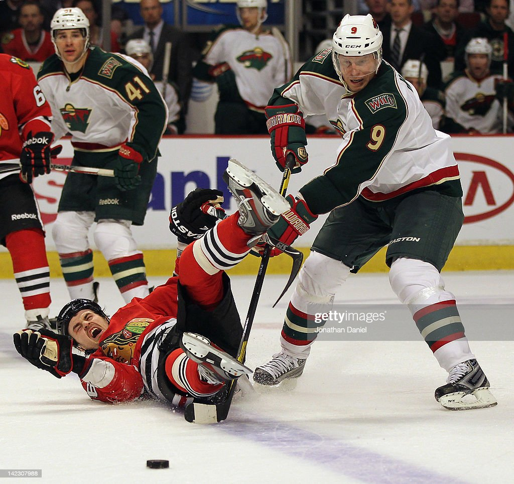 Dave Bolland of the Chicago Blackhawks is dumped to the ice by Mikko Koivu of the Minnesota Wild at the United Center on April 1 2012 in Chicago...
