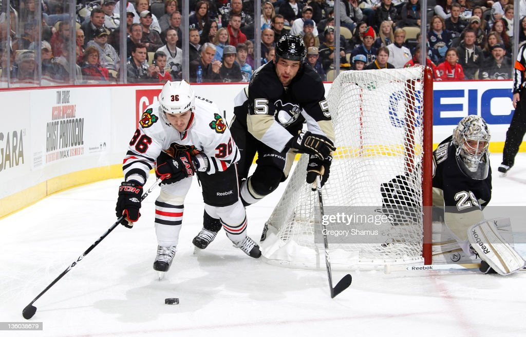 Dave Bolland of the Chicago Blackhawks moves the puck in front of Deryk Engelland and MarcAndre Fleury of the Pittsburgh Penguins on December 20 2011...