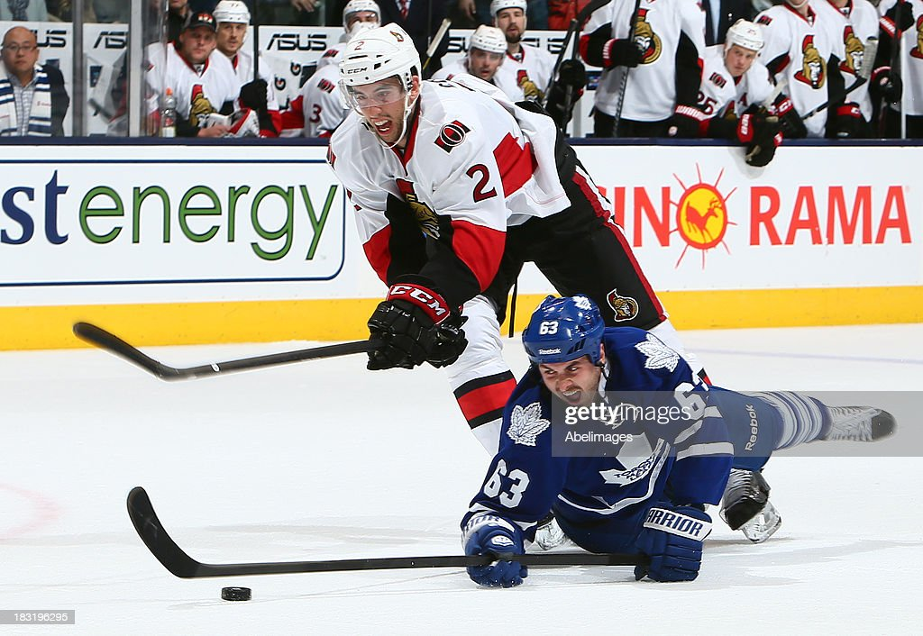 Dave Bolland of the Toronto Maple Leafs gets tripped by Jared Cowen of the Ottawa Senators during the home opener at the Air Canada Centre October 5...
