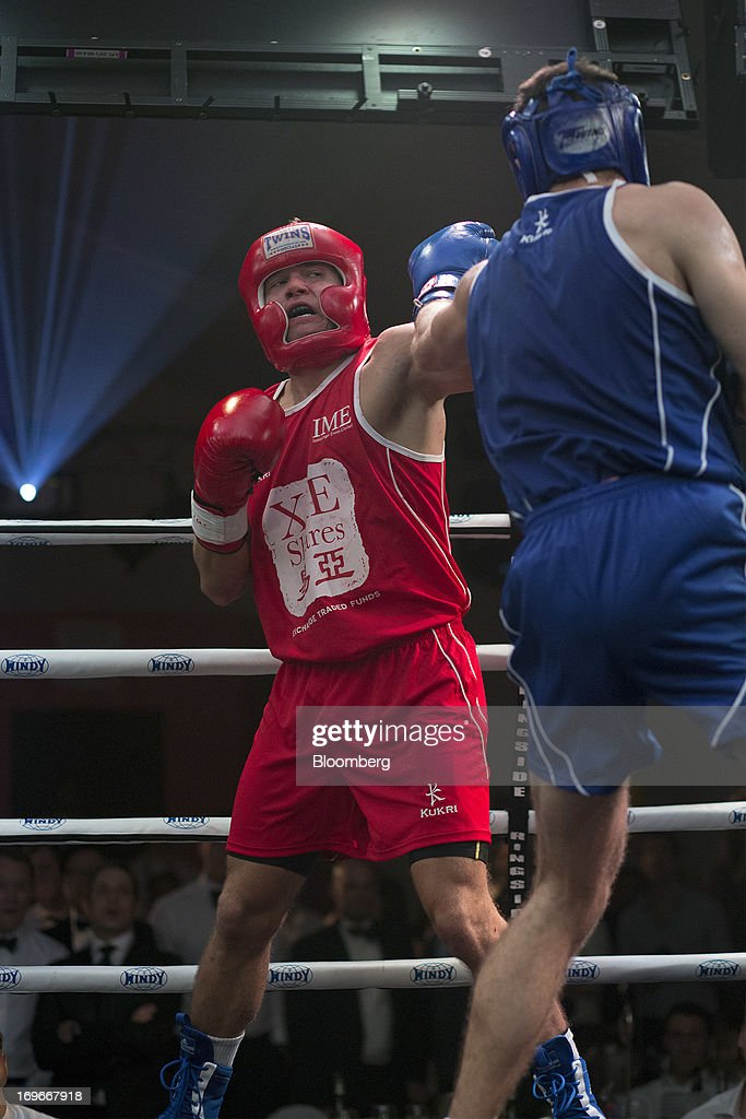 Dave Budden, a senior financial planner at Guardian Life Management Ltd., in red, exchanges blows with Thomas Morrisson, of Deutsche Bank AG equity finance, during the seventh bout of the Hedge Fund Fight Nite 2013 charity fighting event in Hong Kong, China, on Thursday, May 30, 2013. The event raises money for Operation Breakthrough and Operation Smile charities. Budden won the Best Overall title. Photographer: Jerome Favre/Bloomberg via Getty Images