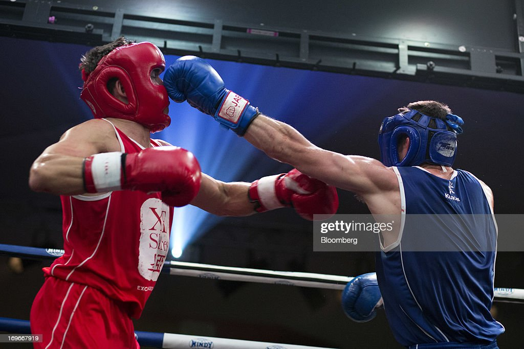 Dave Budden, a senior financial planner at Guardian Life Management Ltd., in red, exchanges blows with Thomas Morrisson, of Deutsche Bank AG equity finance, during the seventh bout during the Hedge Fund Fight Nite 2013 charity fighting event in Hong Kong, China, on Thursday, May 30, 2013. The event raises money for Operation Breakthrough and Operation Smile charities. Budden won the Best Overall title. Photographer: Jerome Favre/Bloomberg via Getty Images
