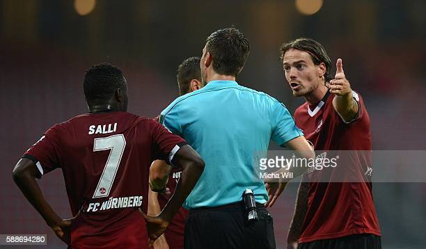 Dave Bulthuis of Nuernberg and his teammates discuss with referee Harm Osmers after the Second Bundesliga match between 1 FC Nuernberg and 1 FC...