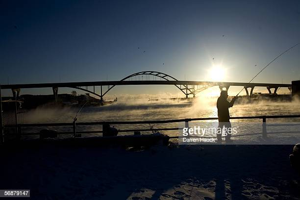 Dave Calvert of Milwaukee casts out a line while fishing at sunrise as 'sea smoke' rises off the Menomonee River February 18 2006 in Milwaukee...