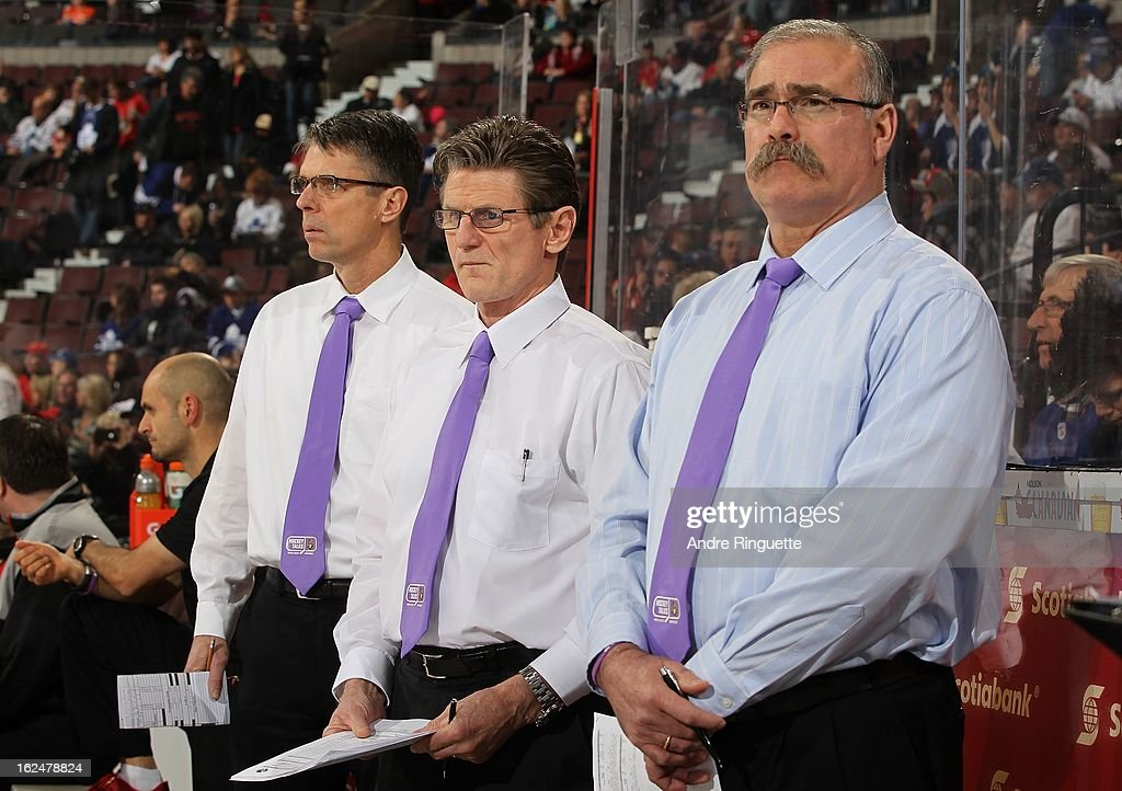 Dave Cameron, Mark Reeds and Paul MacLean of the Ottawa Senators watch warmup while wearing purple ties on Hockey Talks night, in support of Do It For Daron (D.I.F.D.), prior to a game against the Toronto Maple Leafs the Toronto Maple Leafs on February 23, 2013 at Scotiabank Place in Ottawa, Ontario, Canada.