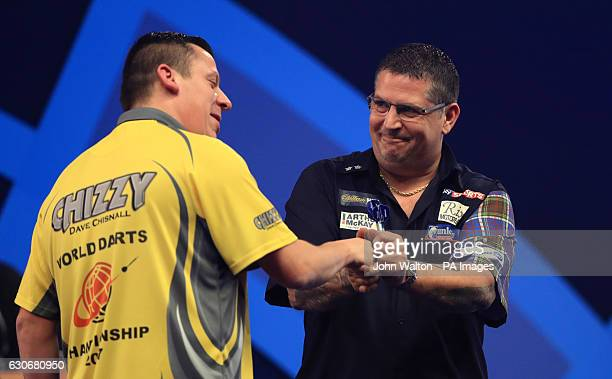 Dave Chisnall congratulates Gary Anderson after his win during day thirteen of the William Hill World Darts Championship at Alexandra Palace London