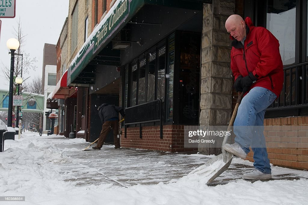 Dave Coffey clears the sidewalk after a winter storm left more than six inches of snow on February 22, 2013 in Iowa City, Iowa. The winter blizzard continues to move across the entire midwest, dumping up to a foot of snow in places as it moves east.