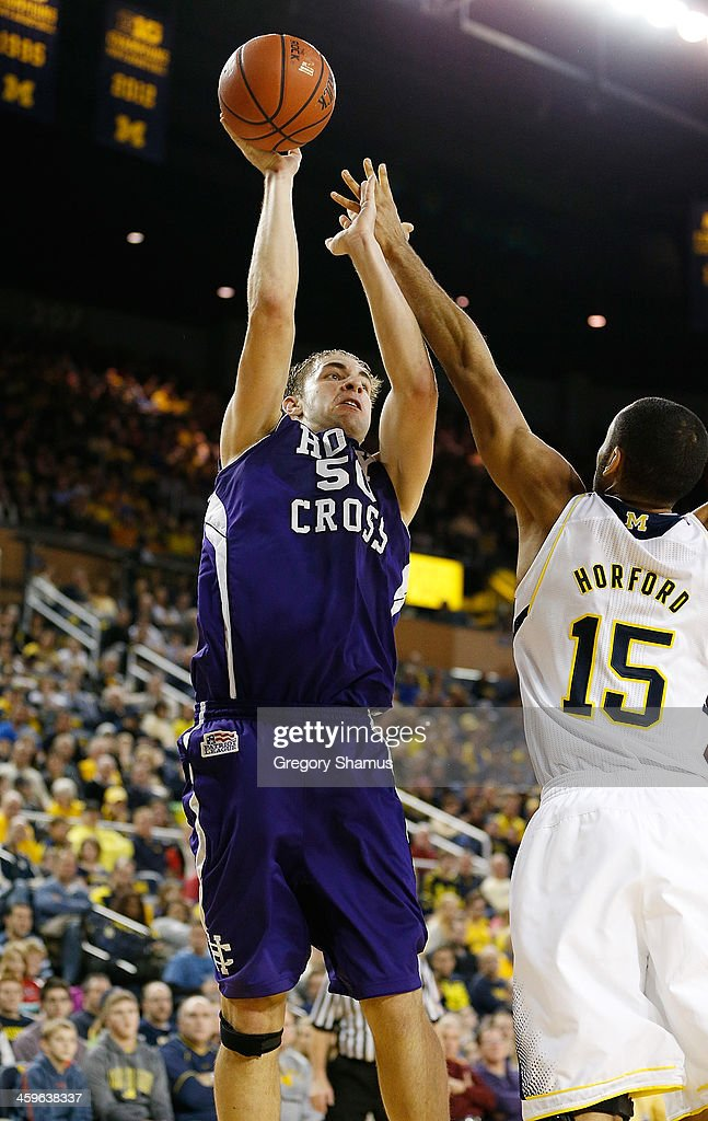 Dave Dudzinski #50 of the Holy Cross Crusaders takes a second-half shot over Jon Horford #15 of the Michigan Wolverines at Crisler Center on December 28, 2013 in Ann Arbor, Michigan. Michigan won the game 88-66.