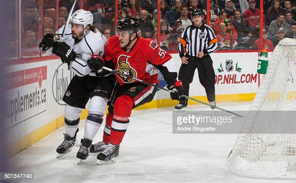 Dave Dziurzynski of the Ottawa Senators body checks Drew Doughty of the Los Angeles Kings against the end boards at Canadian Tire Centre on December...