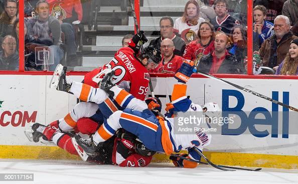 Dave Dziurzynski of the Ottawa Senators bowls over Travis Hamonic and Nick Leddy of the New York Islanders over top of teammate Chris Neil at...