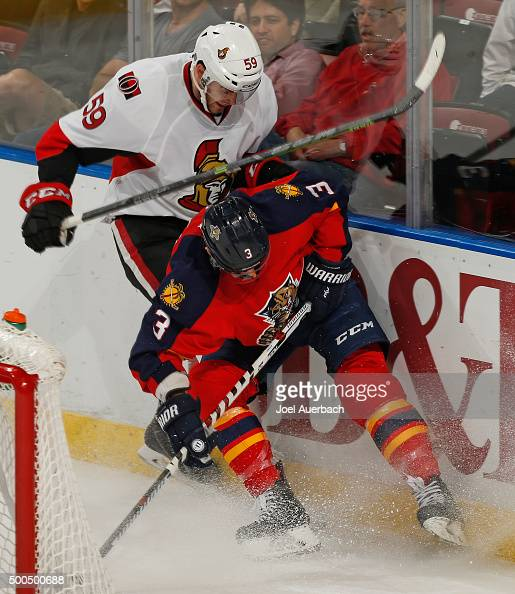 Dave Dziurzynski of the Ottawa Senators checks Steve Kampfer of the Florida Panthers into the boards behind the net at the BBT Center on December 8...