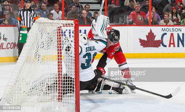 Dave Dziurzynski of the Ottawa Senators collides with Alex Stalock of the San Jose Sharks outside his crease at Canadian Tire Centre on December 18...
