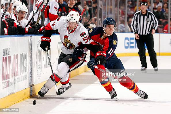 Dave Dziurzynski of the Ottawa Senators digs the puck out from the boards against Jonathan Huberdeau of the Florida Panthers at the BBT Center on...