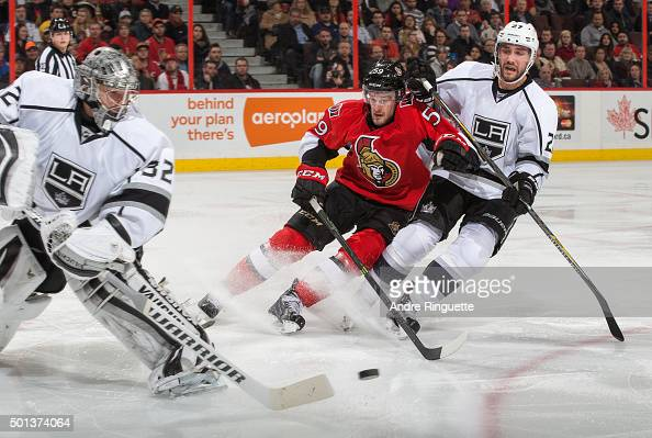 Dave Dziurzynski of the Ottawa Senators drives to the net after the puck against Jonathan Quick and Alec Martinez of the Los Angeles Kings at...