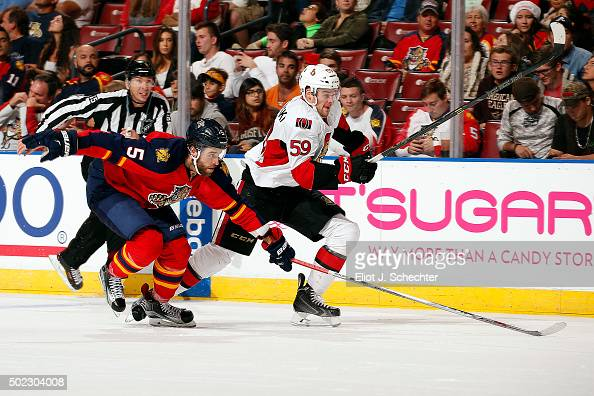 Dave Dziurzynski of the Ottawa Senators skates for possession against Aaron Ekblad of the Florida Panthers at the BBT Center on December 22 2015 in...
