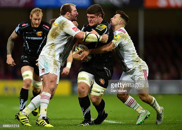 Dave Ewers of Exeter Chiefs is tackled by Joe Marler of Harlequins and Danny Care of Harlequins during the Aviva Premiership match between Exeter...
