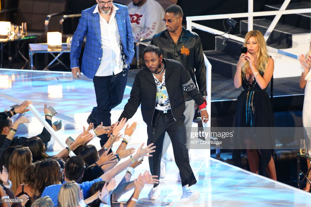 Dave Free, Kendrick Lamar (C), and Dave Meyers receive the Video of the Year award for 'Humble' onstage at the MTV Video Music Awards 2017, In Inglewood, California, on August 27, 2017. / AFP PHOTO / Jean-Baptiste LACROIX