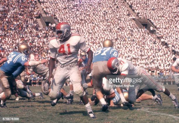 Dave Gibbs of the UCLA Bruins goes for the tackle as Robert Scott and Matthew Swell of the Ohio State Buckeyes block during an NCAA game on October 6...